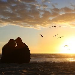 Happy Couple Watching the Sunset in Love on the Beach